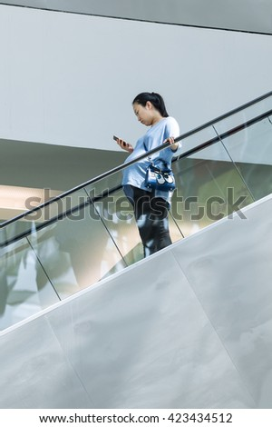 BEIJING-MAY 18, 2016. Pregnant woman on shopping mall escalator. China is concerned over an aging population and shrinking workforce and ended its one-child policy, allow couples having two children.  - stock photo