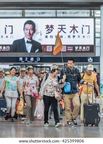 BEIJING-MAY 21, 2016. Tourist group at Beijing Railway Station South, the city's largest station and one of the largest in Asia, terminus for high-speed trains Beijing-Tianjin and Beijing-Shanghai. - stock photo