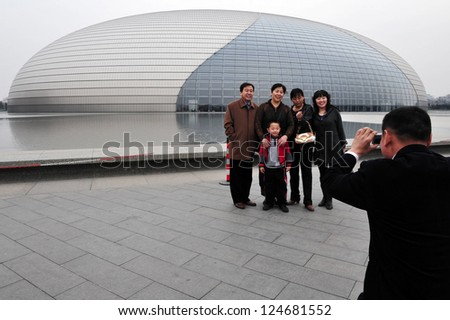 BEIJING-MERCH 15:Visitors at the National Center for the Performing Arts on Mar 15 2009 in Beijing,China.It's made of titanium and glass surrounded by artificial lake and seats 5,452 people in 3 halls - stock photo