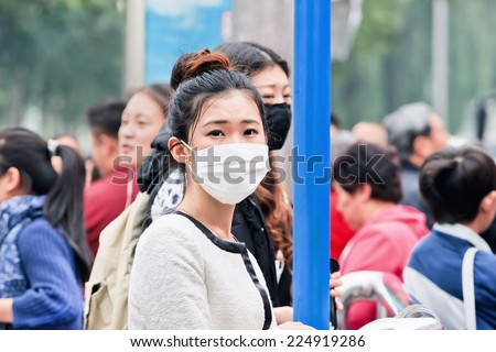 BEIJING-OCT. 19, 2014. Chinese girl with a face mask. Beijing raised its smog alert to orange because the air quality is a health threat. Face masks, once a rarity in Beijing, have now become common. - stock photo