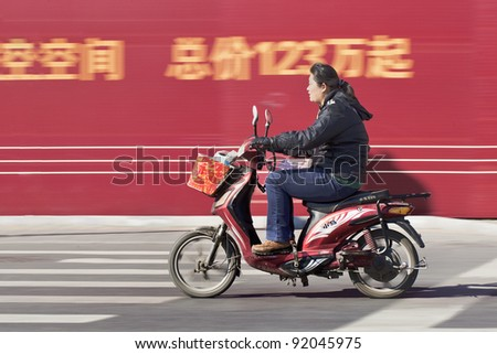 BEIJING - OCT. 25, . Citizen on an electric scooter on Oct. 25, 2011. Electric vehicles have passed cars. Last year, Chinese bought 21 million electric bikes and scooters and 9.4 million cars. - stock photo