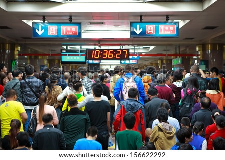 BEIJING-OCT 2: Passengers crowd a subway station during National Day holiday on Oct. 2,2013 in Beijing, China. Beijing's 14 subway lines carry over 8.5 million passengers on an average weekday. - stock photo