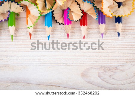 Being creative with pencils and pencil shavings on light wood top view - stock photo