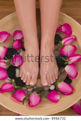 Being pampered by beautiful aromatic pink roses and therapeutic herbal water bath - stock photo