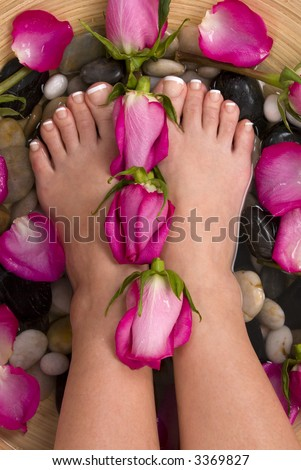 Being pampered by beautiful aromatic pink roses and therapeutic mineral water bath - stock photo