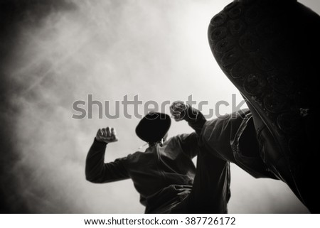 Being punched and mugged by aggressive violent man in hooded jacket on street, victim's pov perspective, monochromatic black and white image. - stock photo