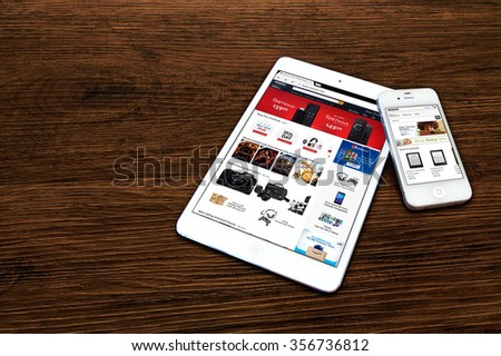 BEKASI, INDONESIA - DECEMBER 31, 2015: Amazon.com website displayed on iPad and its application opened on an iPhone. Amazon.com is the largest Internet-based retailer in the United States. - stock photo