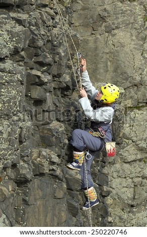 Beklenischevo, Russia - April 29, 2006: Rock climbing Woman rises on the rock by means of a rope and a zhumar up - stock photo