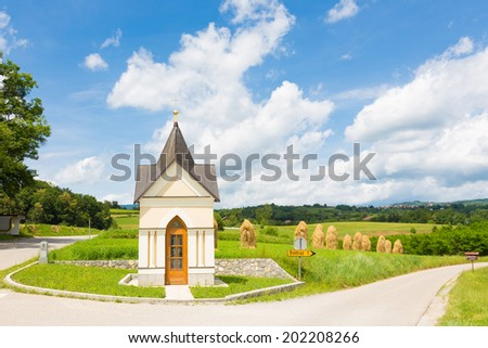 Bela krajina, Slovenia. Traditional christian chapel and hay stacks on the field in the background.