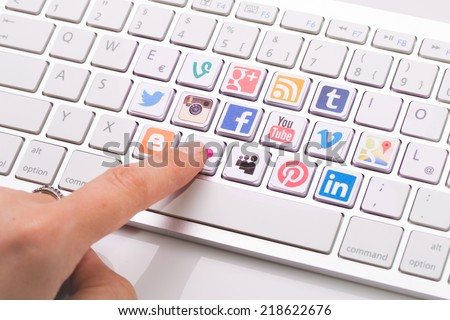 BELCHATOW, POLAND - AUGUST 31, 2014: Male hand pointing on key with a social media logotype collection printed and placed on modern computer keyboard. - stock photo