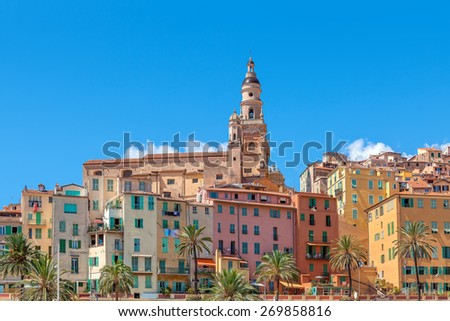 Belfry among colorful houses under blue sky in Menton - small town on French Riviera. - stock photo