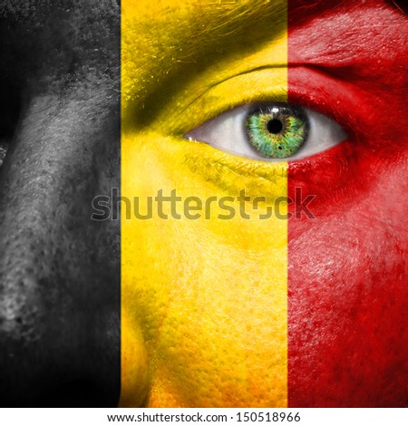 Belgian flag painted on mans face to support his country Belgium - stock photo