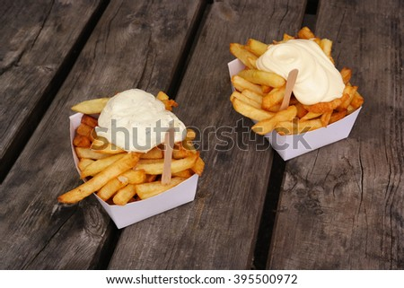 Belgian pommes frites. Two trays of Belgian fries and sauce on top.