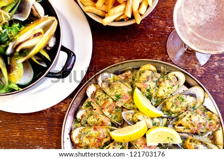 Belgian style grilled mussels with spinac, blue cheese and bacon - stock photo