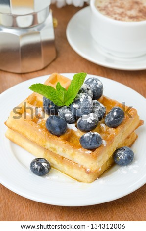 Belgian waffles with blueberries, coffee and fresh fruit for breakfast vertical closeup - stock photo