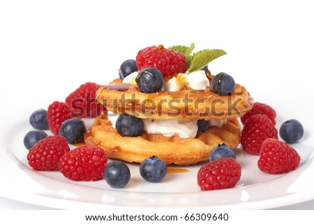 Belgian waffles with fresh raspberries, blueberries, mint leaves and cream on white plate - stock photo