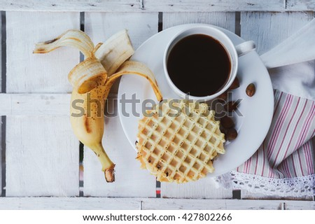 Belgian waffles with peanut butter, bananas and coffee on a wooden background. Delicious breakfast with espresso. Top view - stock photo