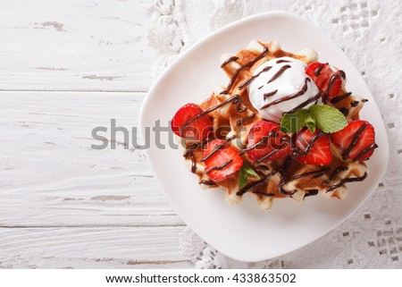 Belgian waffles with strawberries and chocolate topping on a plate. Horizontal view from above