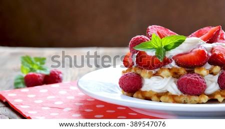 Belgian waffles with strawberries,raspberries and cream. - stock photo