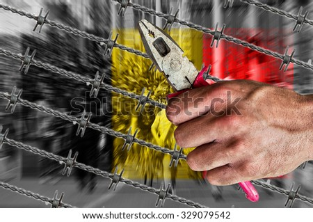 Belgium flag, migrants and barb wire with pliers