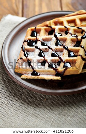 belgium waffles with chocolate topping and sugar powder. On a rustic background with sacking cloth. Vertical shot