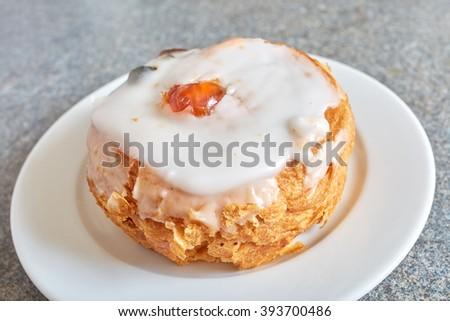 Belgiun bun on white plate, placed on grey kitchen top - stock photo