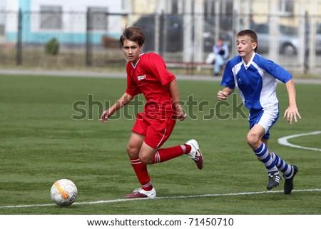 BELGOROD, RUSSIA - AUGUST 21: Unidentified boys plays football on August, 21 2010 in Belgorod, Russia. The final of Chernozemje superiority, Football kinder team of 1996 year of birth. - stock photo
