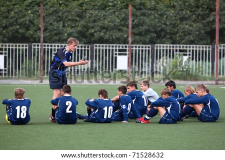 BELGOROD, RUSSIA - AUGUST 20: Unidentified man (coach) with unidentified boys (football players) August, 20 2010 in Belgorod, Russia. The final of Chernozemje superiority, team of 1996 year of birth. - stock photo