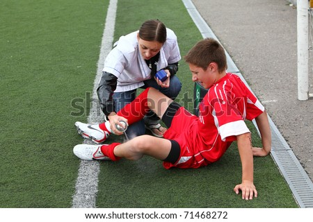 BELGOROD, RUSSIA - AUGUST 20: Unidentified nurse helps to  unidentified boy on football field on August, 20 2010 in Belgorod, Russia. The final of Chernozemje superiority, team of 1996 year of birth. - stock photo