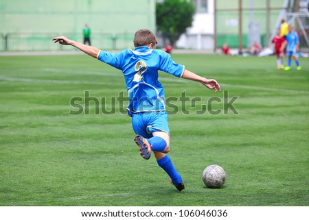 "BELGOROD, RUSSIA - JUNE 17: Unidentified boy from football team ""Kursk"" making pass on June 17, 2012 in Belgorod, Russia. Chernozemie Superiority. Football team of 2001 year of birth. - stock photo"