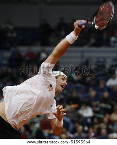 BELGRADE - MARCH 7: John Isner returns the ball during the Davis Cup World Group first round tennis match against Novak Djokovici in Belgrade Arena March 7, 2010 in Belgrade, Serbia. - stock photo