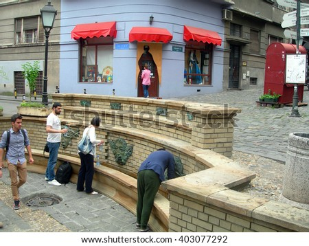 BELGRADE-MAY 13: Unidentified people fill water bottles from historic, artistic water fountains in historic district Skadarlija in capital Belgrade, Serbia on May 13, 2015.