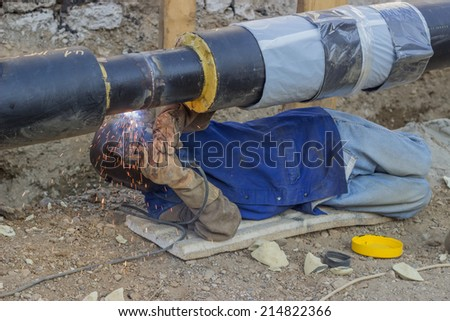 BELGRADE, SERBIA - AUGUST 14: Welder welding underground steel pipe kneels on ground. Pipe is supported by crane. Pipe is tack welded. Selective focus. At street Vojvode Stepe in August 2014. - stock photo