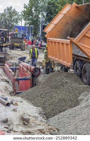 BELGRADE, SERBIA - AUGUST 09: Workers and dumper truck backfilling trench for the ground piping. At construction site in August 2014. - stock photo