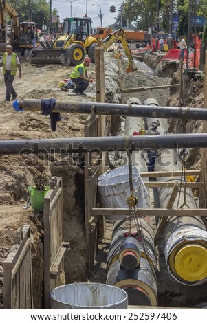 BELGRADE, SERBIA - AUGUST 09: Workers and excavators digging trench for the ground piping. At construction site in August 2014.  - stock photo
