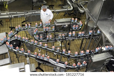 BELGRADE, SERBIA - CIRCA APRIL 2013: Worker observes milk products line at dairy, circa April 2013 in Belgrade - stock photo