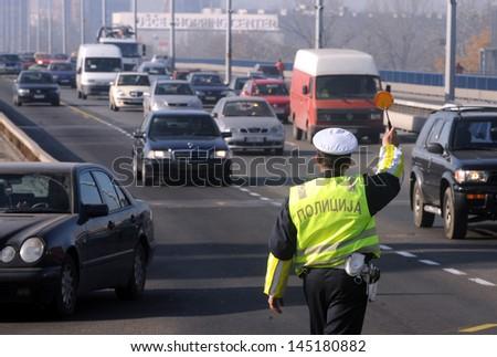 BELGRADE, SERBIA - CIRCA NOVEMBER 2009: Policeman stops the vehicle circa November 2009 in Belgrade - stock photo