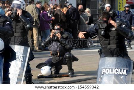 """BELGRADE, SERBIA - CIRCA OCTOBER 2010: Policeman wears gas mask in street riots at """"Belgrade Pride"""" circa October 2010 in Belgrade - stock photo"""