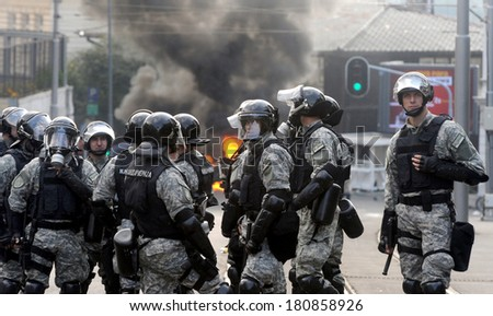 """BELGRADE, SERBIA - CIRCA OCTOBER 2010: Special force police watches burning police car after riots at """"Belgrade Pride"""" circa October 2010 in Belgrade - stock photo"""