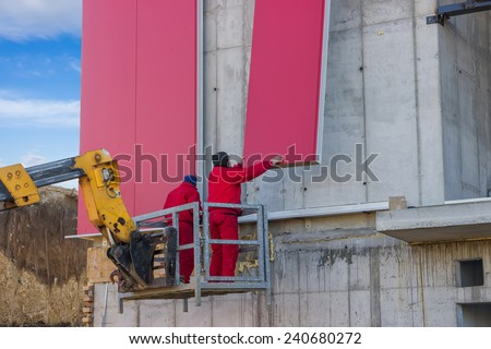 BELGRADE, SERBIA - DECEMBER 27: Builders on aerial access platform connecting red wall sandwich panels. At construction site in December 2014.
