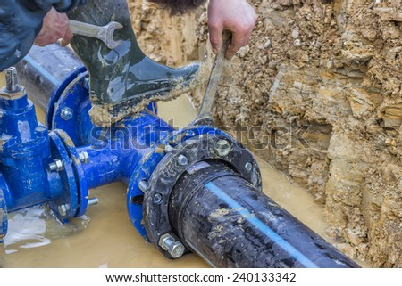 BELGRADE, SERBIA - DECEMBER 23: Close up of installing water pipe valve in a trench. Laying a water pipeline, working on water valves. Selective focus. At construction site in December 2014.  - stock photo