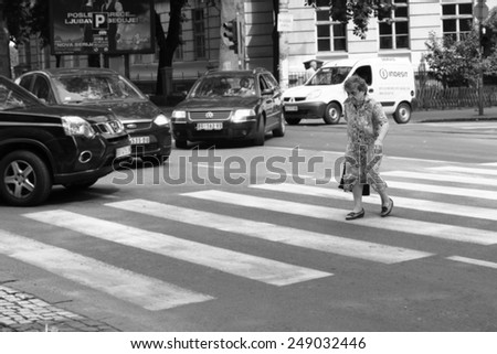 BELGRADE, SERBIA - JULY 30: an elderly woman crosses the street on a crosswalk with many cars stops. Shot in 2014 - stock photo