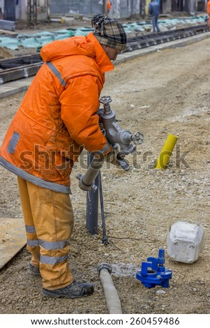 BELGRADE, SERBIA - MARCH 08: Worker connects fire hydrant. At street Vojvode Stepe in March 2015.