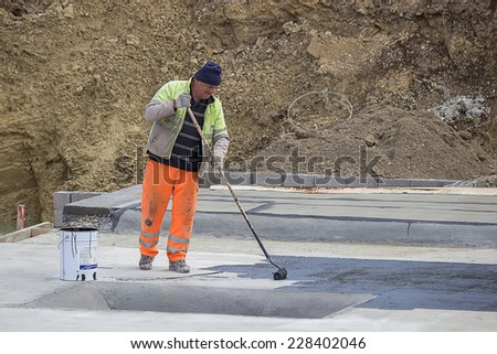 BELGRADE, SERBIA - OCTOBER 29: Builder workers at floor slab insulation work, insulation material over concrete slabs to keep water out. At construction site in October 2014.