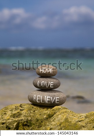 Believe, hope and love rock on beach