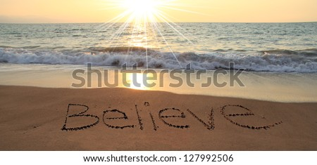 Believe written in the sand at the beach - stock photo