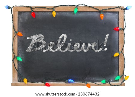 Believe written in white chalk on a black chalkboard surrounded with colored lights and isolated on white - stock photo