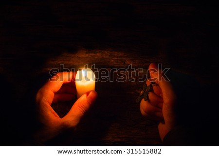 believes man with a candle and a cross selective focus - stock photo