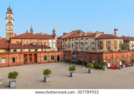 Bell tower among old houses in small town of racconigi in Piedmont, Italy. - stock photo