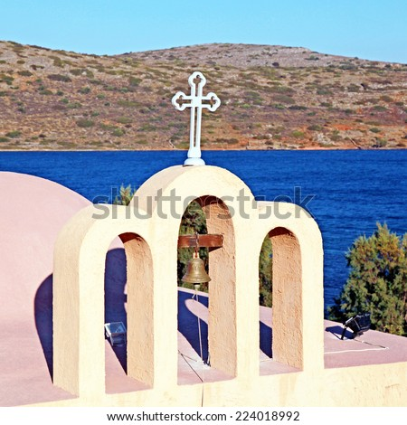 bell tower of a little classical orthodox Greek church with view of Mediterranean sea (Crete,Greece). - stock photo